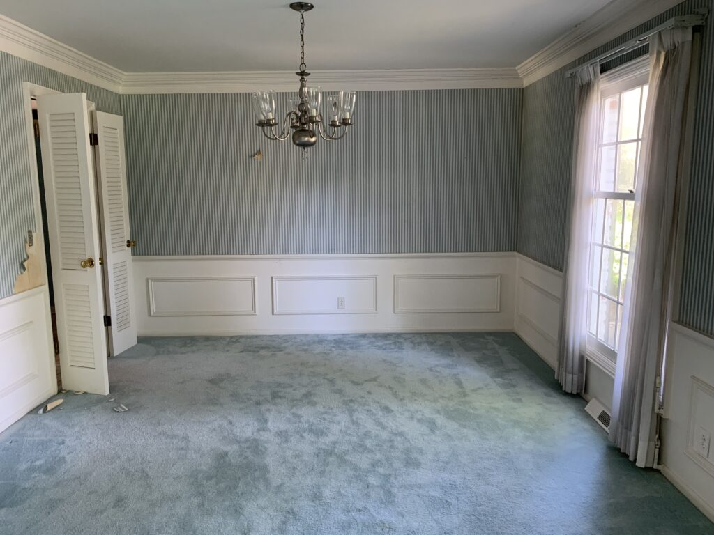 The formal dining room with blue carpet.